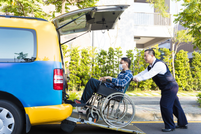 driver helping man on wheelchair getting into car