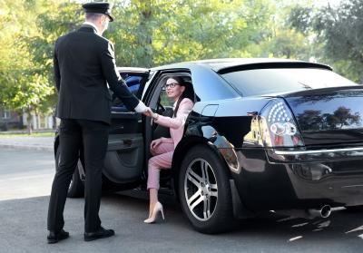 chauffeur opening car door for businesswoman