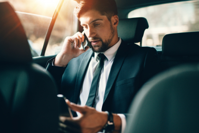 young businessman talking on mobile phone while sitting on back seat of a car.