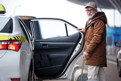 portrait of positive bearded old man in glasses going to sit into the car